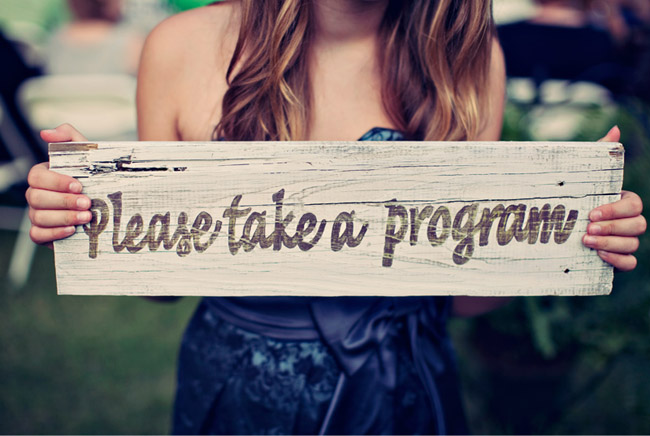 "Wooden sign painted with the words ""Please take a program"""