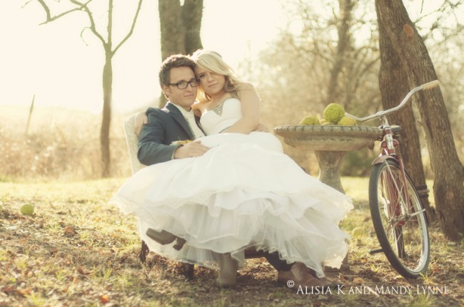 Bride sits on grooms lap with bicycle standing next to them. Beautiful sunset backdrop