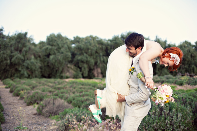 Groom carrying bride over his shoulder. Bride wearing strapless empire waist gown with flower applique in hair and carrying pink, white yellow bouquet and teal and white colored shoes  and groom wearing tan suit with dark tie and yellow boutonniere
