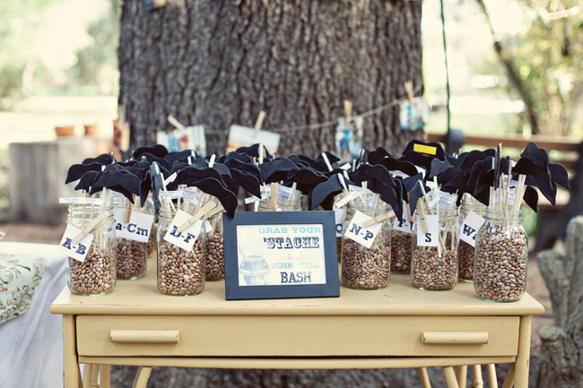 "Clear jars full of small rocks and mustaches on Popsicle sticks for guest to take.  A sign in a black frame that says ""Grab your ''stache, join the bash"""