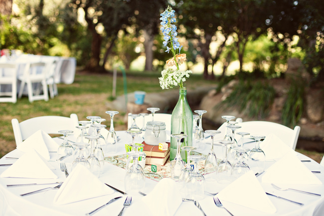 White outdoor wedding reception table with folded white napkins. Vintage books and green clear vase with white and blue flowers for centerpiece