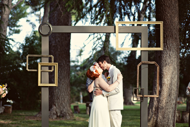 Whimsical DIY Wedding picture frame backdrop with bride and groom kissing underneath