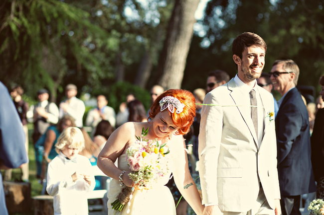 Bride and groom standing during ceremony.  Bride laughing with flower applique  in her hair holding pink, green and yellow bouquet.  Groom wearing tan suit with a big grin.