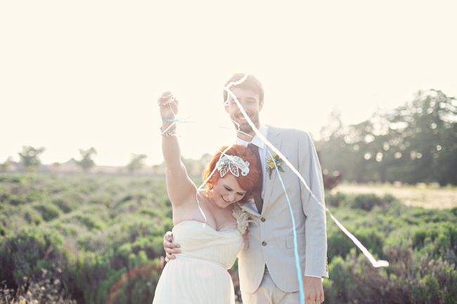 Bride wearing strapless empire waist gown and groom wearing tan suit with dark tie and yellow boutonniere standing in field holding up streamers