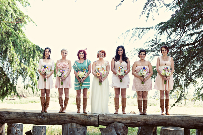 Bridesmaids in brown boots and pink dresses standing on log holding purple, white, pink flower bouquets and bride standing in the middle