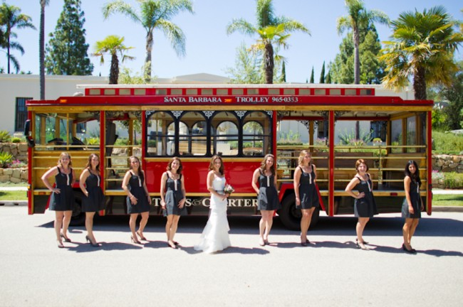 bridesmaids in dark color dress stand with bride in front of old Santa Barbara trolley
