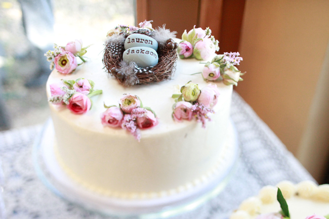 wedding cake with mini roses and a birdnest cake topper with fake robin eggs