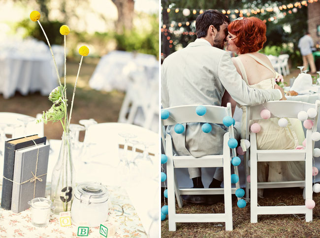 Outdoor Wedding reception table with clear vase with black number 3 sticker for table number and 3 yellow billy ball flowers with 2 vintage books tied with twine and centerpieces. (Left photo); Bride and groom kissing at reception table sitting in white folded chairs with blue and pink styrofoam balls garland around  chair.