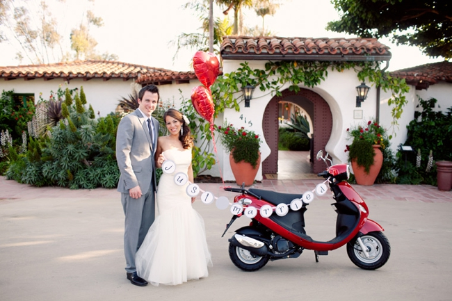 """Bride and Groom stand next to red Vespa with """"Just Married"""" sign attached"""
