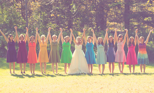 Bride standing with bridesmaids holding their hands up wearing rainbow colored bridesmaids dresses