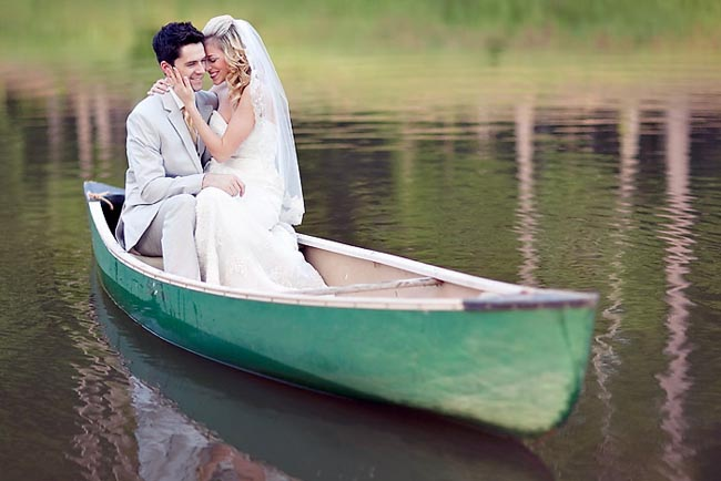 Bride and groom in green canoe on lake in Peachtree, Georgia