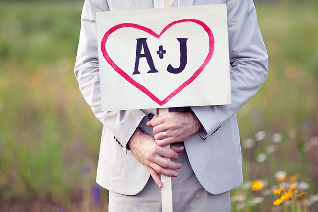 Groom holding a painted sign that says A+J with heart