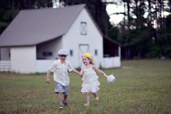 boy and girl running in front of white barn