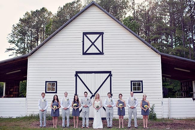 Elegant Southern barn wedding bridal party in front of white barn