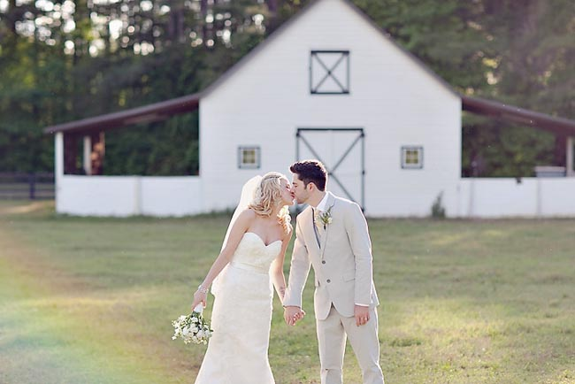Bride and groom kiss with white barn in background