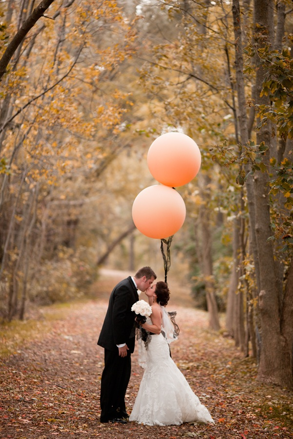 bride and groom with peach balloons in woods