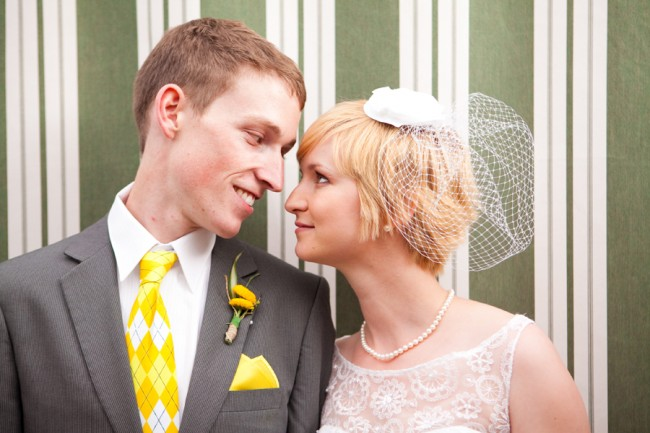 closeup photo of bride in birdcage veil looking into eyes of groom with yellow argyle tie