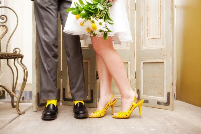 Bride in bright yellow heels, groom with black shoes and yellow socks