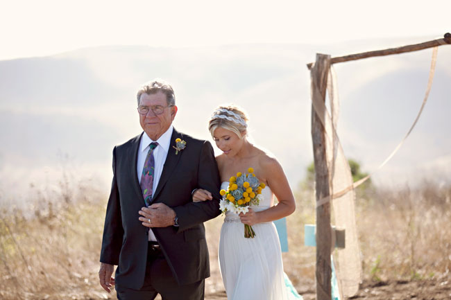 bride and father walk down outdoor aisle