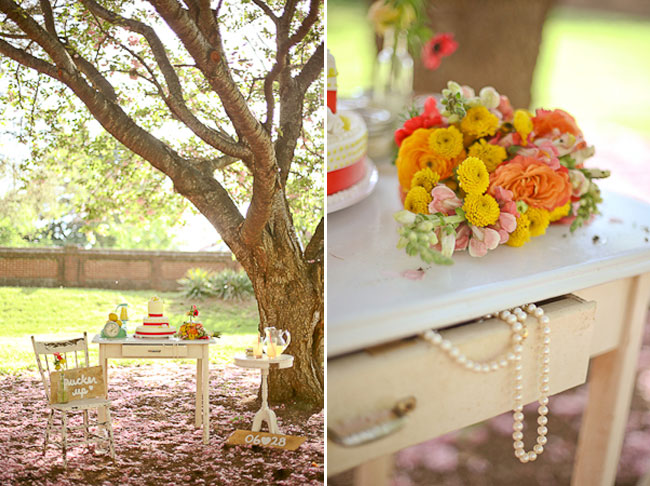 vintage white furniture with lemon dot cake, flowers, and signs sit under cherry blossom tree