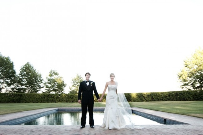 Bride and groom hold hands in front of pond at Beaulieu Gardens