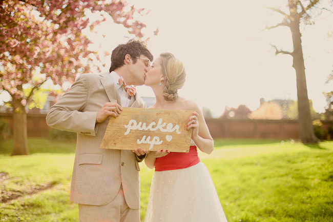 "styled shoot couple kiss while holding painted sign that says ""Pucker up"""