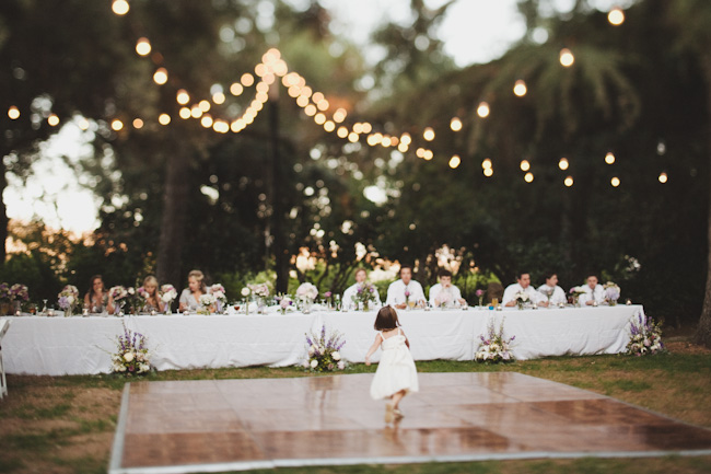 flower girl dancing on outdoor wedding reception dance floor with head table in background