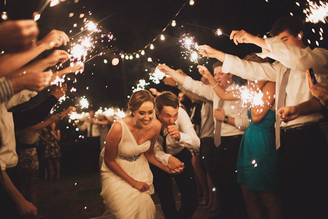 bride and groom duck under sparkler send off at night