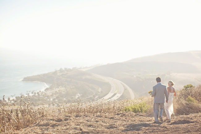 bride and groom stand on dirt hill overlooking Santa Barbara coast line