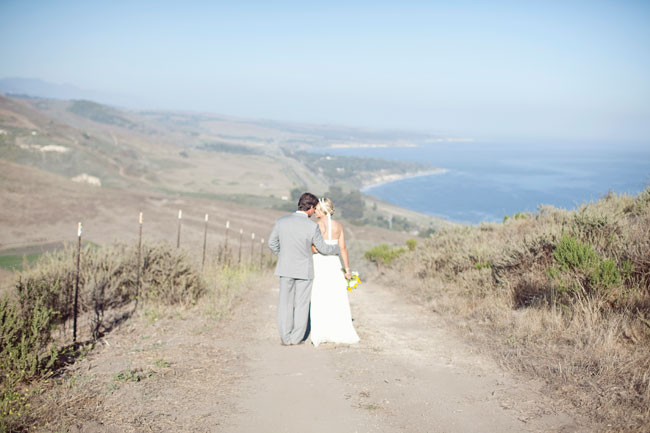 bride and groom stand on dirt path overlooking coast of California