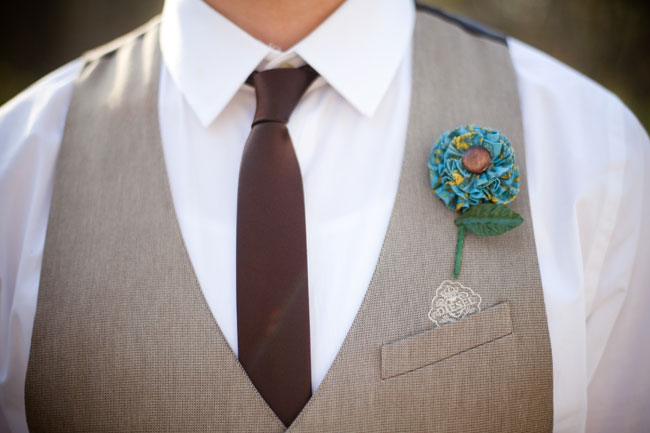 Groom with gray vest, chocolate brown necktie, and homemade boutonniere
