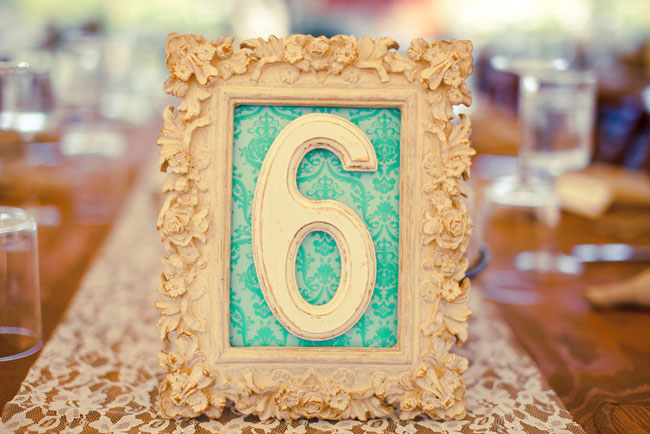Wedding reception table number 6 in a white ornate frame on a lace table runner