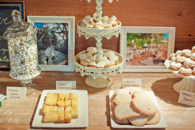 Wedding reception dessert table with picture frames and ornate dessert stand