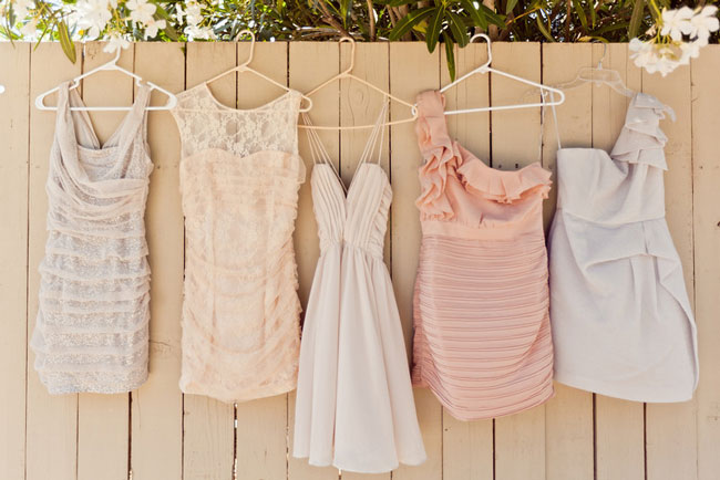 Pink, white, lace short brides maids dresses hanging on fence