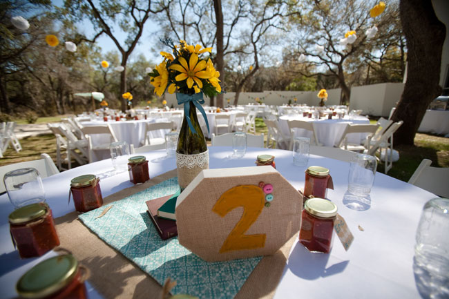 outdoor yellow wedding table with homemade wooden signs and yellow flowers on table