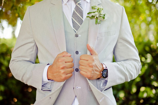Groom in grey suite and stripped grey and white tie