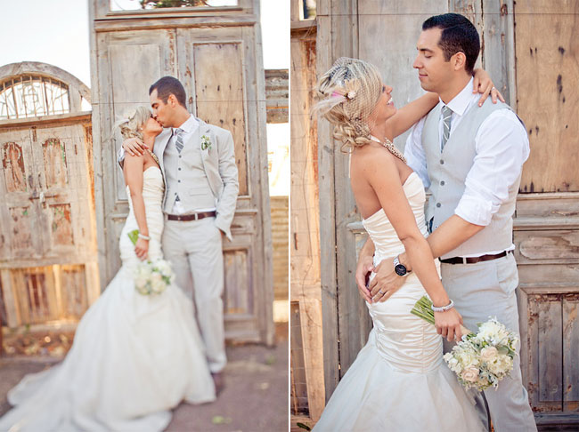 Bride and groom kissing in front of vintage doors at Cornerstone Gardens