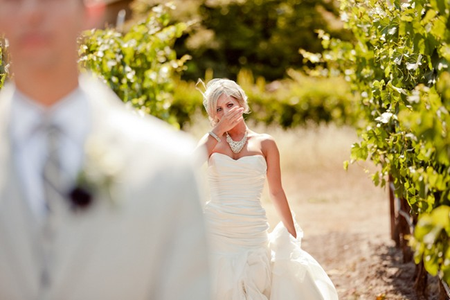 Bride walking up to groom for first look in the vinyard at Cornerstone Gardens