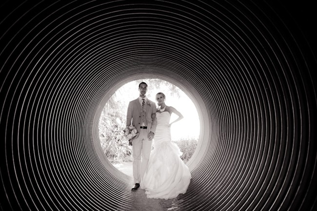 bride and groom standing in tunel at corner stone gardens