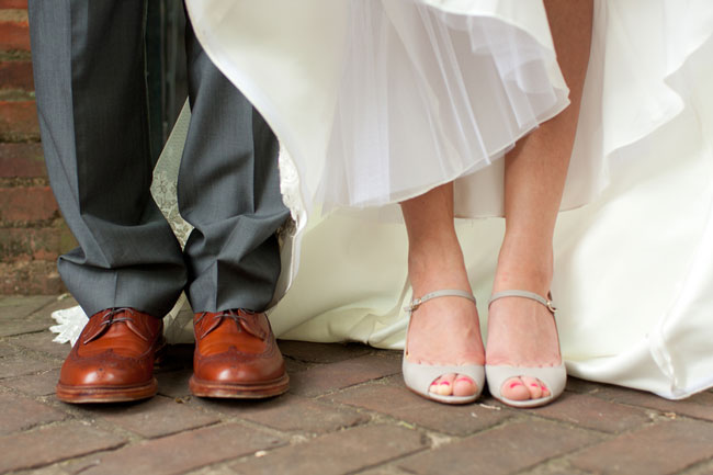 Groom wearing gray suit and brown dress shoe. Bride wearing beige peep toe heals with strap