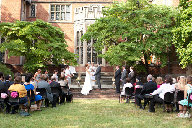 Bride and groom standing together holding hands during wedding at Virginia Center for Architecture with guests sitting in black seats on lawn
