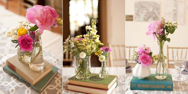 Wedding ceremony table at Virginia Center for Architecture with pin, white and yellow flowers in clear vases atop of vintage books on white and gray patterned table runner