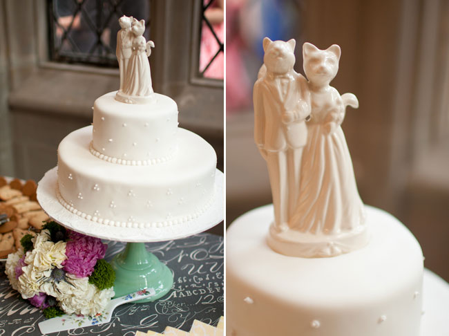 2-Tier white wedding cake with swiss dot pattern on green cake stand with a squirrel and cat bride and groom cake topper on grey table cloth (Right photo); squirrel and cat bride and groom cake topper