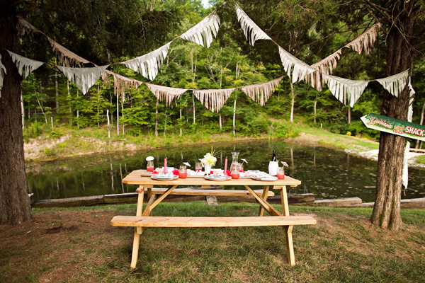 picnic table with food on it and bunting streamers overhead
