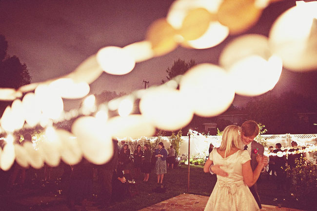 Bride and groom dancing under night sky