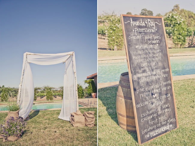 vineyard wedding at Sogno Del Fiore ceremony with large chalkboard sign standing against a wine barrel. Vineyard in background