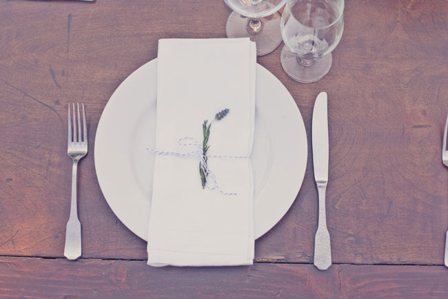 Overhead photo of single dried lavender wrapped with string around white napkin set on dark wood table