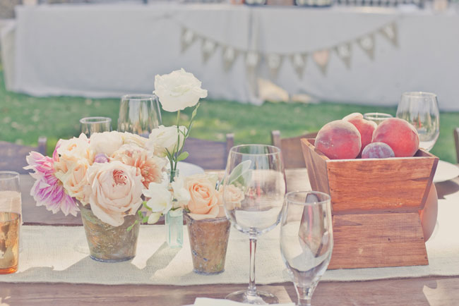 simple centerpiece of peaches in wood container with peach color flowers