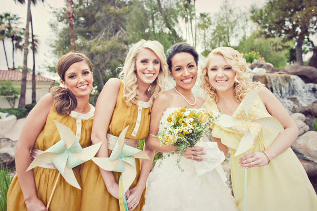 bride and bridesmaids in yellow holding pinwheels