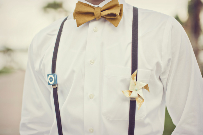 groomsman in suspenders with mustard yellow bowtie and pinwheel boutonniere